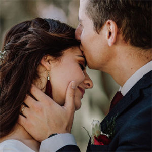 Reeds Country Lodge, Close shot of groom kissing bride on her forehead on their wedding day while caressing her cheek
