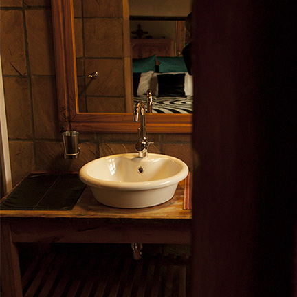 A beautiful basin with a bed reflected in the mirror above it