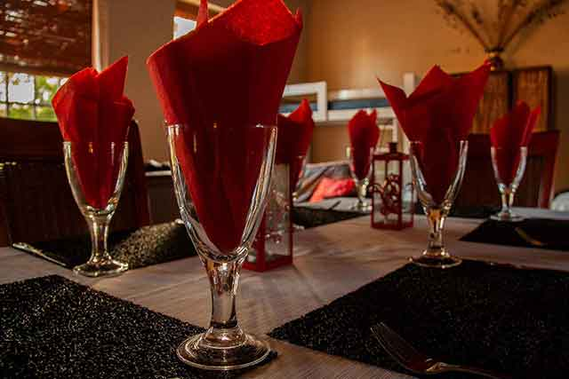 Worcester accommodation, a table of wine glasses with red serviettes in Reeds Country Lodge's self catering family unit
