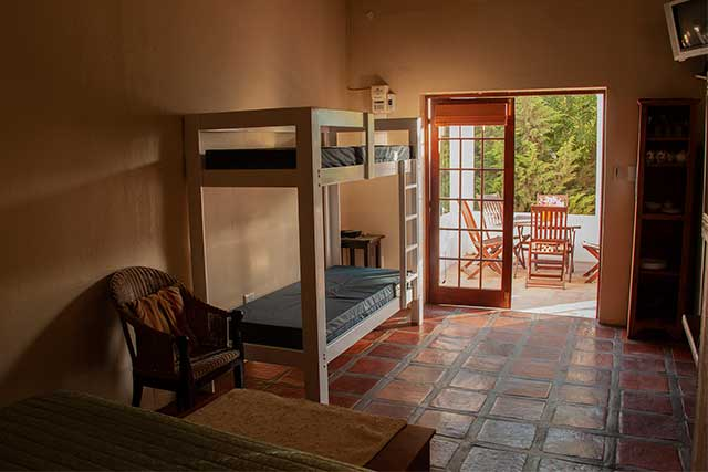 A bunk bed on the left of big open doors opening up to a porch at Reeds Country Lodge