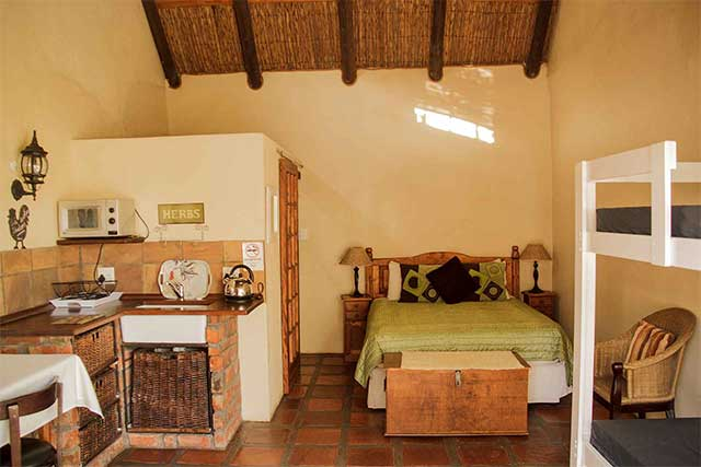A high ceiling apartment with a kitchenette, queen size bed and thatched roof