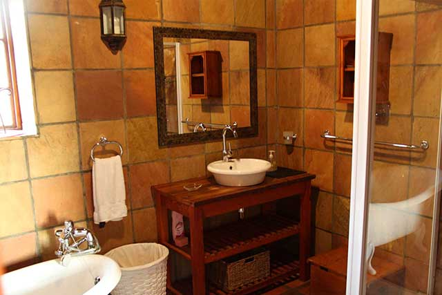 A victorian style bathroom with victorian bath, shower and basin with beautiful finishings at Reeds Country Lodge family accommodation
