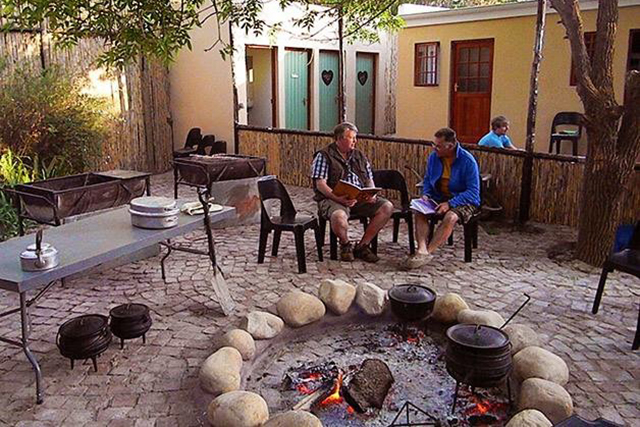 Worcester Accommodation, Two guests visiting around the open fire potjiekos at Camp Reed unit at Reeds Country Lodge