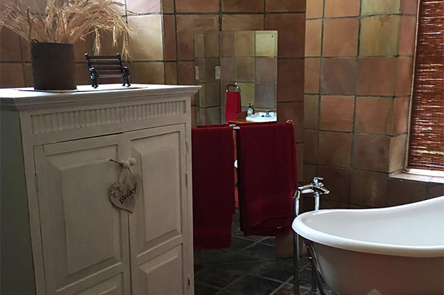 An ensuite bathroom with victorian bath, mirror and white cupboard at Reeds Country Lodge