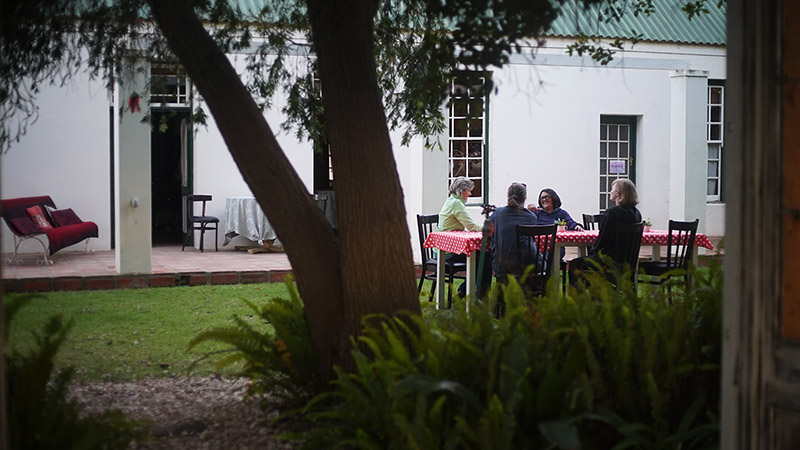A group of guests relaxing at a table on the lawn at Reeds Country Lodge
