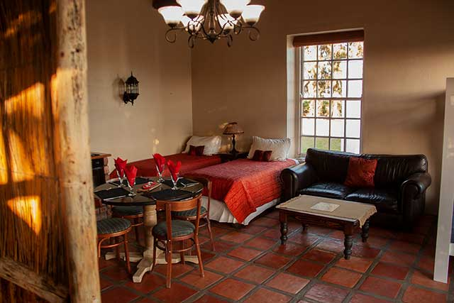 A family unit with big windows, cute dining table, leather couch and twin bed