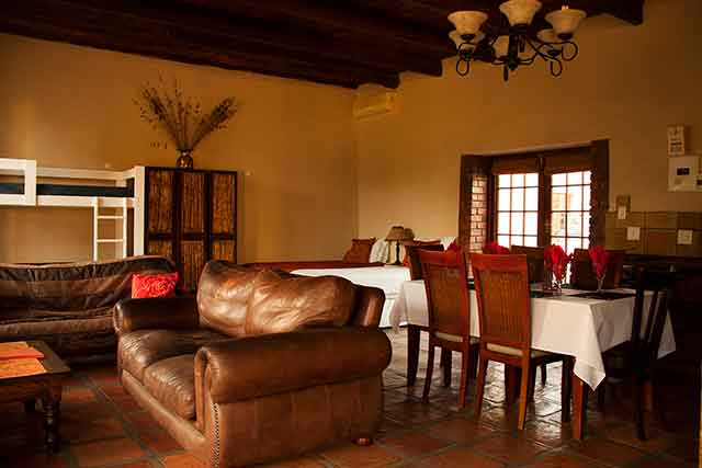 Accommodation, Open plan family accommodation unit with leather couch and table laid at Reeds Country Lodge
