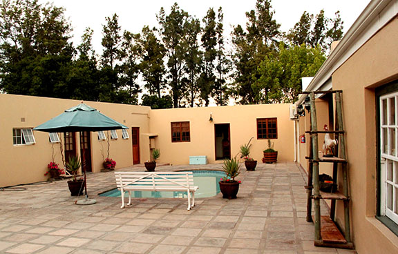 A court yard with a small swimming pool and umbrella at Reeds Country Lodge Conference Venue