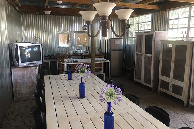 A white long table for gathering in a fully equipped tin kitchen with a television in the back