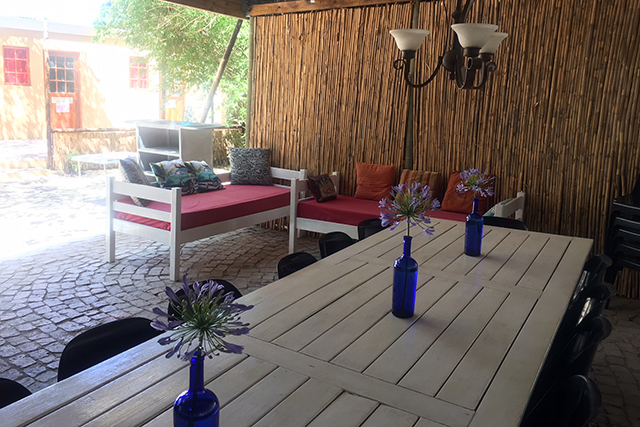 A long white table with comfy couches for launching and visiting in the tin kitchen at Reeds Country Lodge